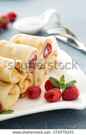 Crepes filled with cottage cheese and raspberry for breakfast - stock photo