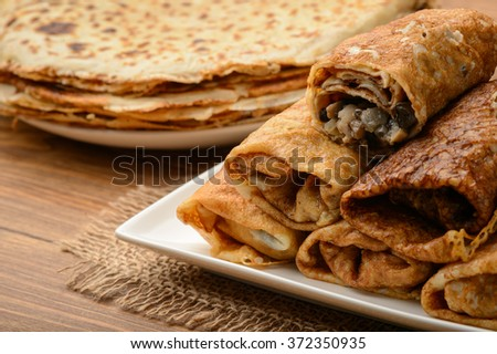 Crepes stuffed with chicken and mushrooms on wooden table. - stock photo