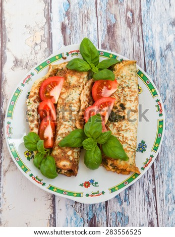Crepes stuffed with spinach, basil, cheese and tomatoes on an old wooden table, top view - stock photo