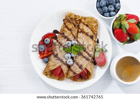 crepes with berries and chocolate sauce for breakfast, top view, closeup - stock photo