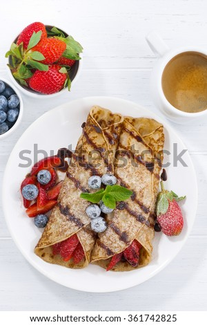 crepes with berries and chocolate sauce for breakfast, vertical, top view, closeup - stock photo