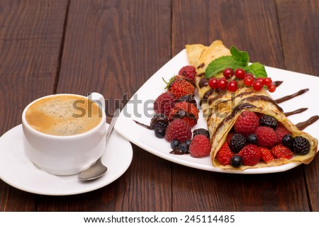 Crepes With Berries and cup of coffee .Crepe with Strawberry, Raspberry, Blueberry and Chocolate topping. Pancake - stock photo