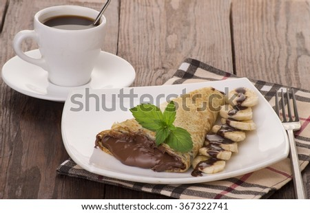 Crepes with chocolate cream and banana - stock photo