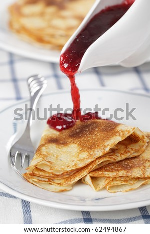 Crepes with cranberry jam on white plate closeup - stock photo
