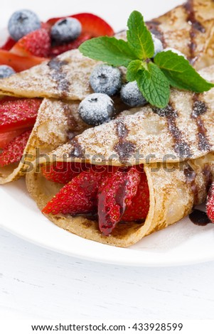 crepes with fresh berries and chocolate sauce, closeup - stock photo