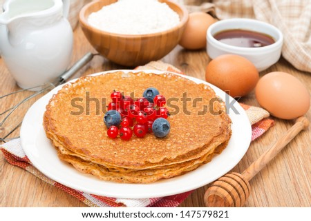 crepes with fresh berries and ingredients for baking on a wooden table, close-up - stock photo