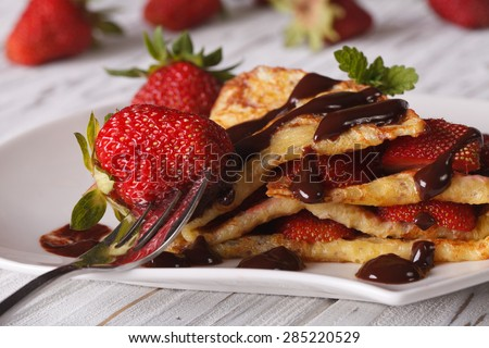 Crepes with fresh strawberries and chocolate topping macro on a plate. horizontal