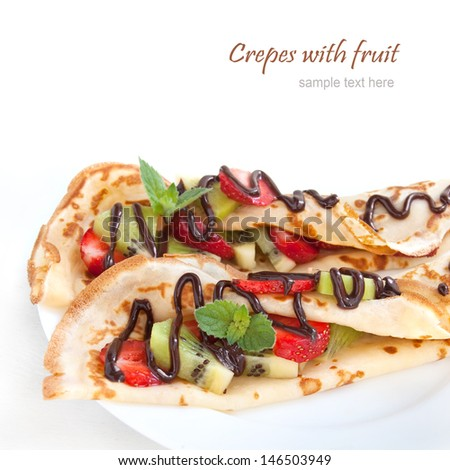 Crepes with fresh strawberries and kiwi with chocolate topping on the white plate - stock photo