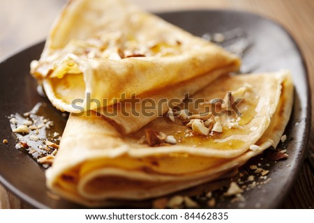 crepes with honey or syrup and roasted nuts - stock photo