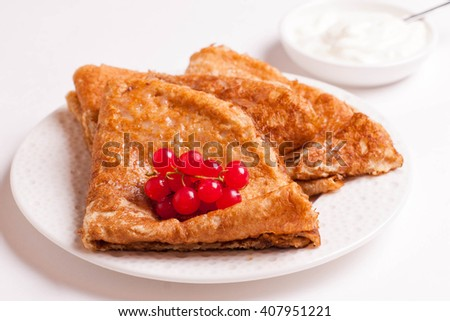 crepes with red currants and sour cream on a plate isolated on white, close up, horizontal