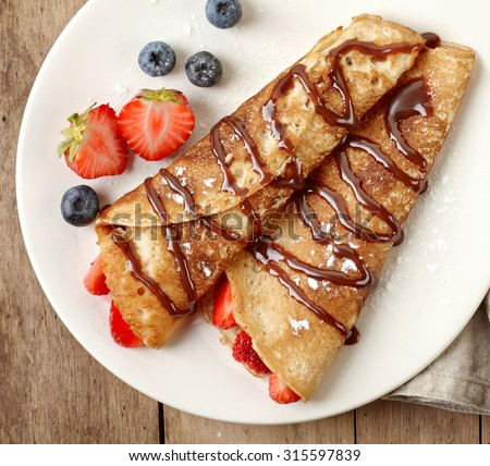 Crepes with strawberries and chocolate sauce - stock photo