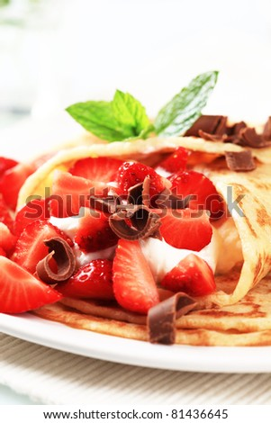 Crepes with sweet cheese and strawberries sprinkled with chocolate curls