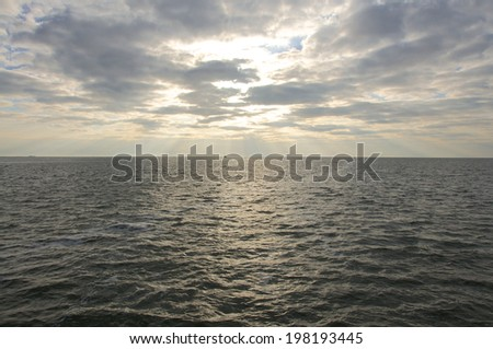 Crepuscular rays in the North Sea. A Trawler in the wadden Sea. Shrimp fishing is one of the oldest cultural techniques in the fisheries in the North Sea - stock photo