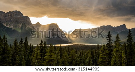 Crepuscular rays shine through clouds over Hector Lake in Banff National Park, Canada.