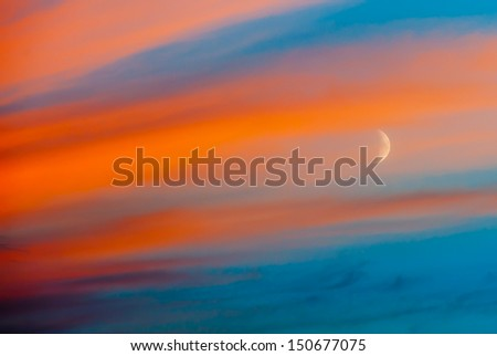 Crescent in blue sky with orange clouds, sunset