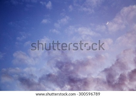 Crescent moon in cloudy sky - stock photo