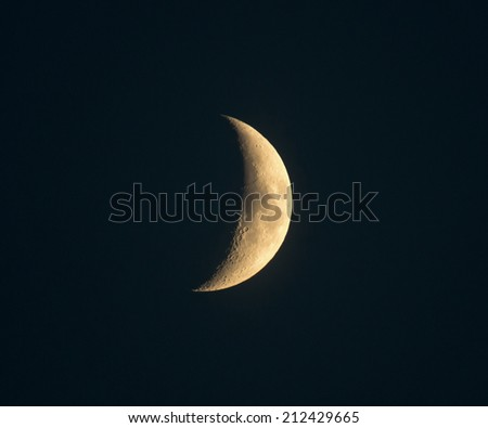 Crescent moon with craters visible in sky not quite black - stock photo