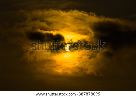 Crescent sun or sun eclipse in cloudy sky, yellow and dark tone
