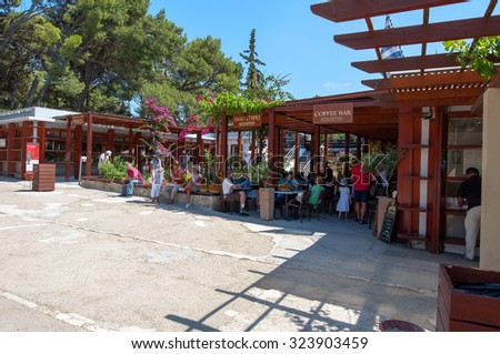 CRETE,GREECE-JULY 21: Tourists have a rest in a cafe at the Knossos palace on July 21,2014. Knossos is the largest Bronze Age archaeological site on Crete and is considered Europe's oldest city.