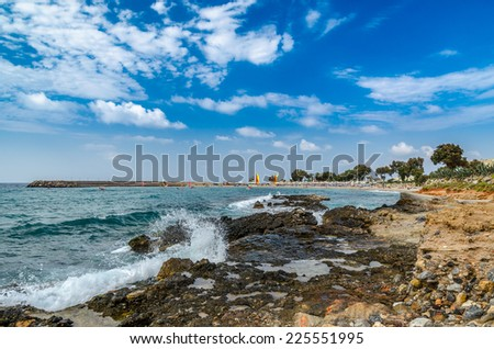 Crete island, Greece - August 22, 2013: Beautiful Cretan rocky coastline with blue sea and surfers at the background near Sisi town.