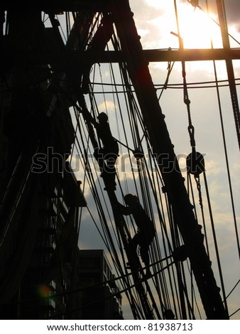 Crew climbing the rigging of a tall ship at dusk - stock photo