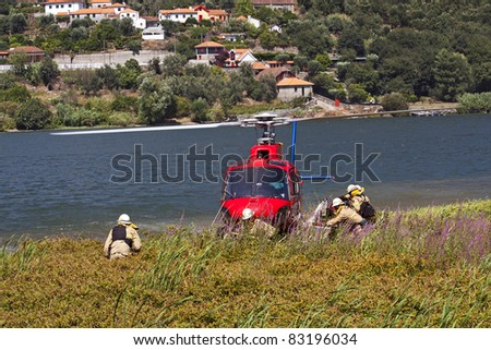 Crew of firefighters working on the helicopter stopped on the banks of the River Douro - stock photo