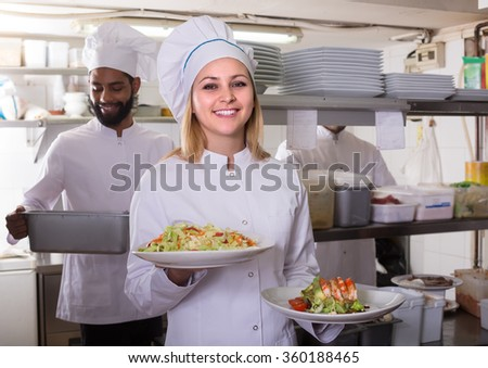 Crew of happy russian professional cooks working at restaurant kitchen  - stock photo