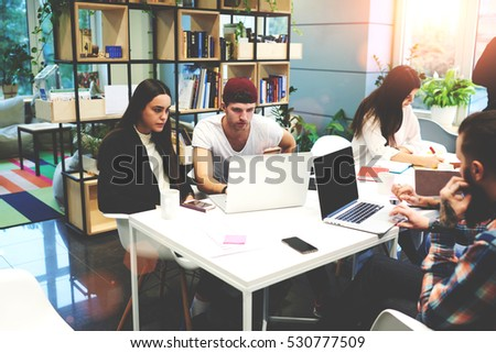 Crew of skilled international male and female student making rating of best social networks in web using laptop computer with mock up screen connected to internet sitting in modern university library