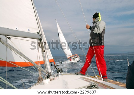 Crewman looking into other sailing ship - stock photo