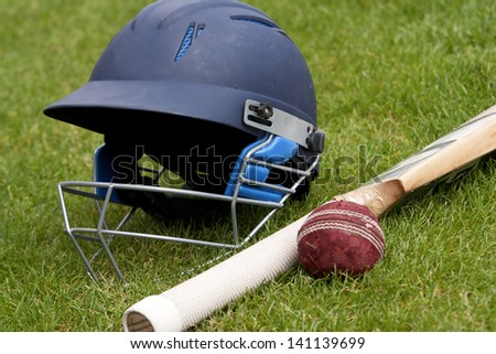 Cricket ball, bat and helmet on green grass of cricket pitch - stock photo