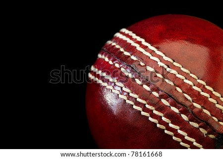 Cricket ball in close-up, over black background.  Shallow depth of field.