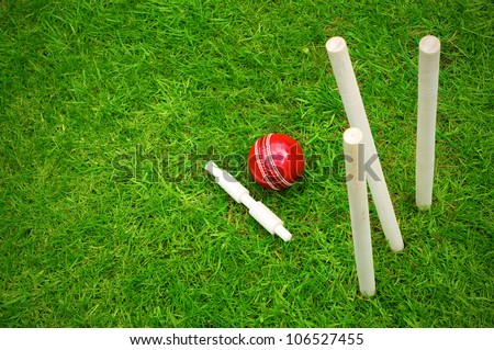 cricket ball on pitch after hitting stumps with copy space - stock photo