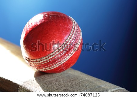 Cricket ball resting on a cricket bat with blue background - stock photo
