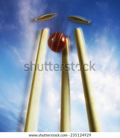 Cricket Ball Striking Wicket and Knocking Off Bails - stock photo