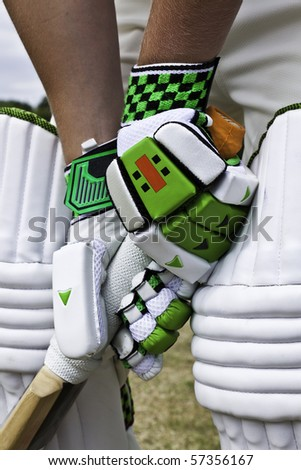 Cricket batsman stood at the crease wearing protective gloves and pads