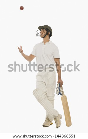 Cricket batsman tossing a cricket ball - stock photo