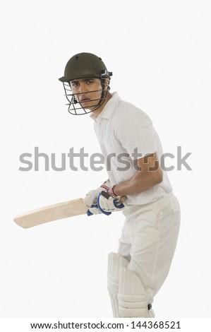 Cricket batsman with a high back lift - stock photo