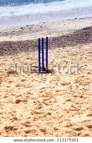 Cricket wickets  and a bat in the sand with sea in the back ground - stock photo