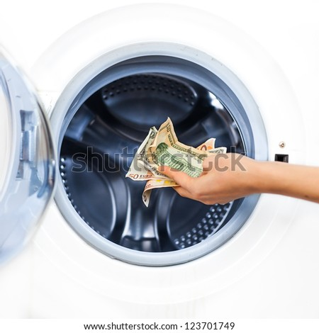 Crime Concept of Money Laundry: detail  of a hand putting money into the laundry machine - stock photo