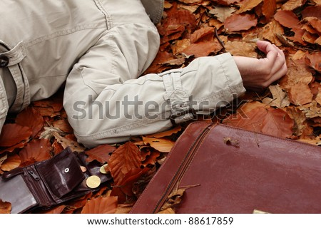 Crime in the woods.  A body, an open wallet and a briefcase. - stock photo