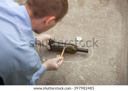 crime investigation. evidence at the crime scene. fingerprints on the bottle. - stock photo