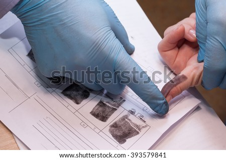 crime investigation. expert takes fingerprints of a suspect in a crime. - stock photo
