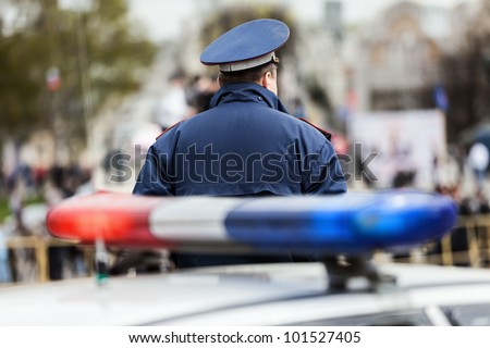 Crime law security service officer cop guarding street near police car with siren light - stock photo