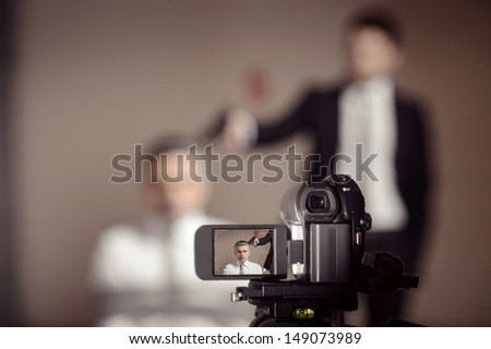 Crime scene.  Close-up of home video camera shooting a man in formalwear aiming a tied-up businessman - stock photo