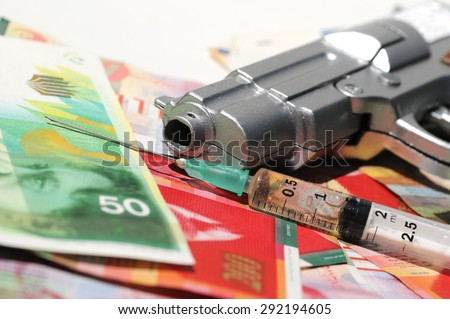Crime scene drugs by injection and weapons on banknotes of New Israeli Shekels (NIS) - stock photo