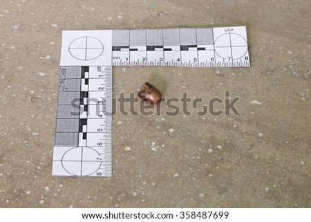 Crime scene, empty bullets casings on ground with scale ruler - stock photo