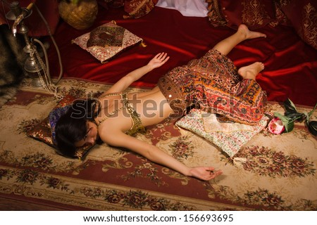 Crime scene imitation: lifeless woman in a traditional oriental costume lying on a floor