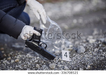 Crime scene investigation - collecting pistol on forest way - stock photo