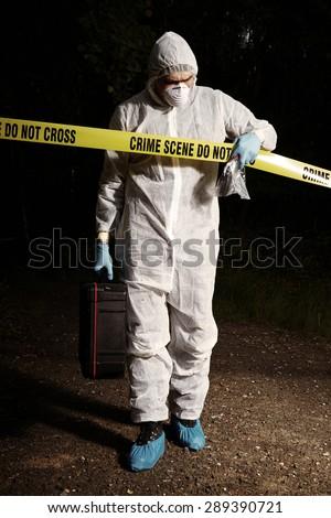 Crime scene investigation - criminologist leaving night crime scene - stock photo