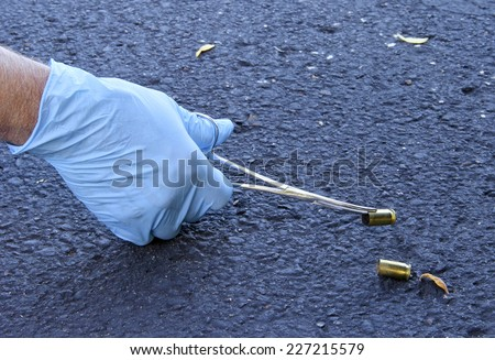 Crime scene investigator is gathering evidence by picking up shell casing using rubber gloves and a forcepts. - stock photo